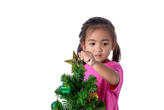 Happy asian child holding gold star for decoration christmas tree. Premium Photo