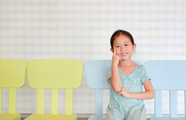 Happy asian child preschool girl in a kindergarten room poses on plastic baby chair. Premium Photo