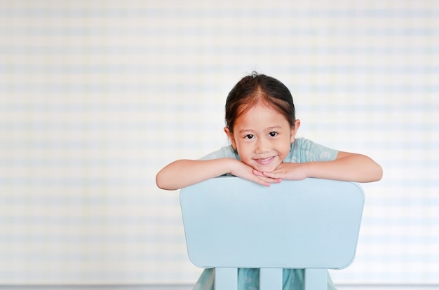 Happy asian child preschool girl in a kindergarten room poses on plastic baby chair. Premium Photo
