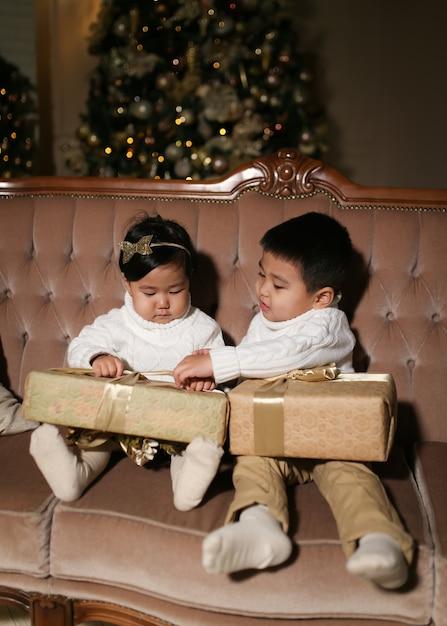 家の木のそばのソファに座って、開いて笑って、贈り物を与える幸せなアジアの子供たち Premium写真