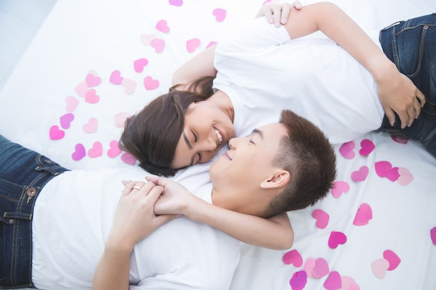 Happy asian couple on the bed at home Free Photo