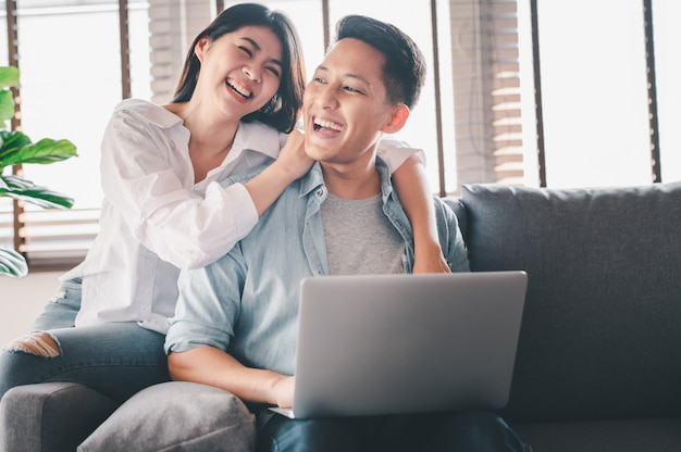 Happy asian couple in love laughing while using laptop Premium Photo