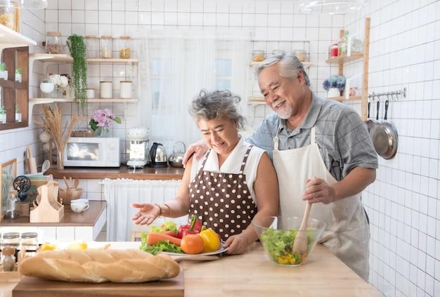 Счастливые азиатские старшие старшие пары варя свежую еду в кухне дома. Premium Фотографии