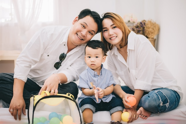 Happy asian family, father and mother and son in living room