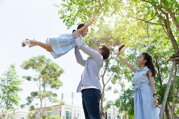 Happy asian family. father throws up daughter in the sky in a park at natural sunlight and house. family vacation concept Premium Photo