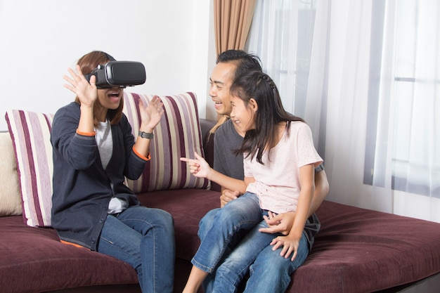 Happy asian family at home wearing virtual reality goggles Premium Photo