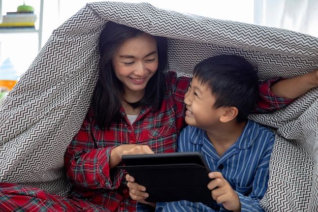 A happy asian family mother and son do activity together in living room playing game on digital tablet. Premium Photo