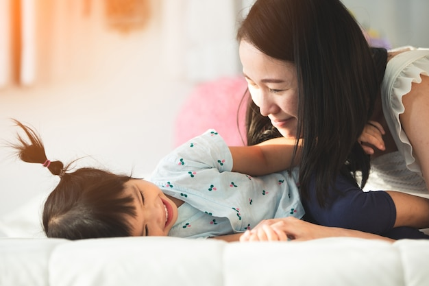 Happy asian family mother with daughter playing on bed with smile face. Premium Photo