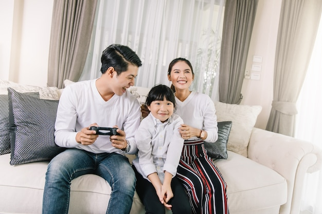 Happy asian family playing video games at home and having fun together. Premium Photo