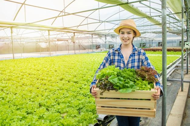 Happy asian farmer gardener woman hand hold basket of fresh green organic vegetable in greenhouse hydroponic organic farm,small business entrepreneur concept Premium Photo