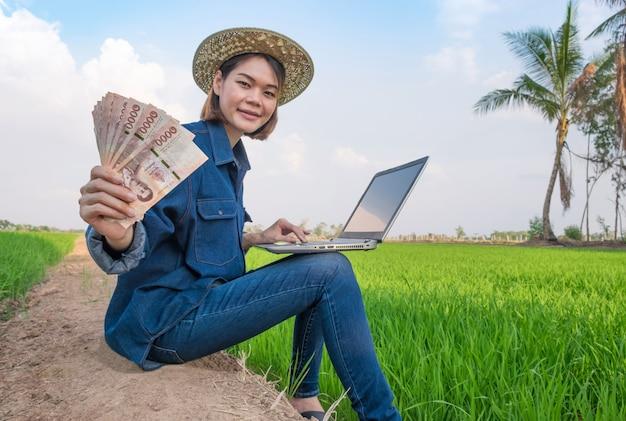 Happy asian farmer woman sitting and using laptop computer with holding banknote money at green rice farm Premium Photo