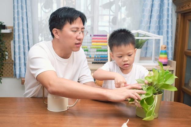 Счастливые азиатские отец и сын веселятся, режут кусок растения в гостиной дома, знакомят детей с навыками ножниц, обучают на дому, занимаются домашним садоводством Premium Фотографии