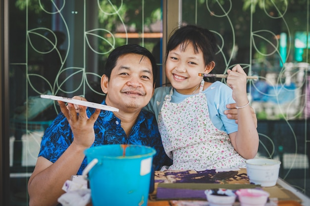 Счастливый азиатский день отца. забавный улыбающийся отец и ее дочь, живопись и рисунок акварелью Premium Фотографии
