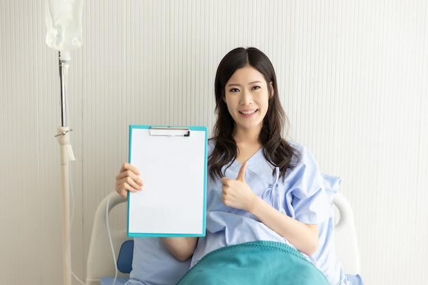 Happy asian girl on a hospital bed with a blank paper Premium Photo