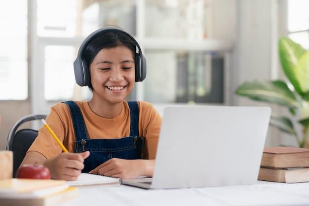 自宅でオンライン学習幸せなアジアの女の子 Premium写真