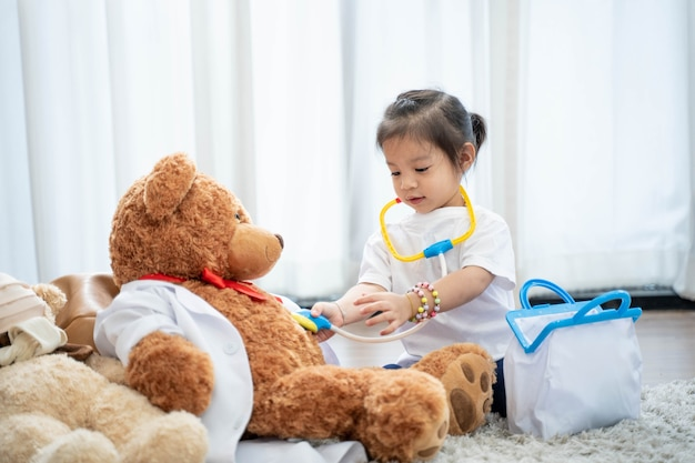 A happy asian girl playing doctor or nurse listening a stethoscope to toy. Premium Photo