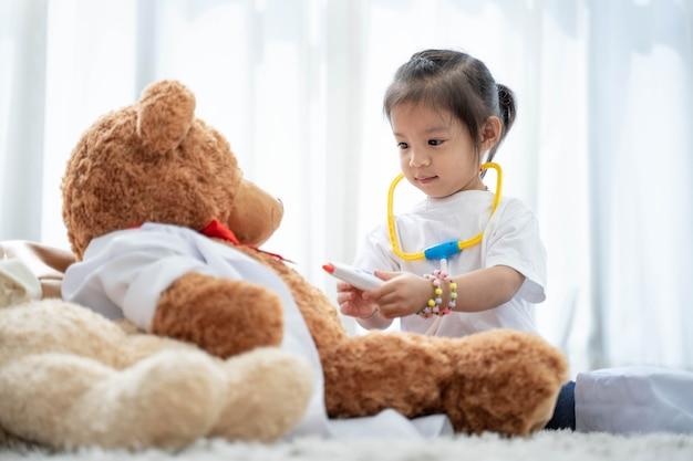 A happy asian girl playing teddy bear Premium Photo