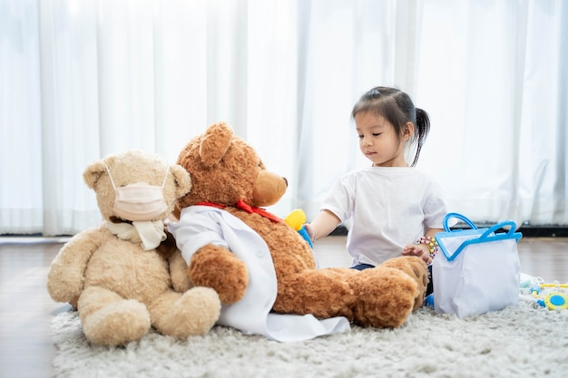 A happy asian girl playing teddy bear Premium Photo