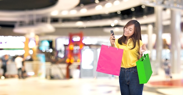 새로운 정상적인 디지털 라이프 스타일 (클리핑 경로 포함)에서 스마트 폰으로 온라인 쇼핑과 함께 종이 쇼핑백에 행복 아시아 소녀 Resive 주문 프리미엄 사진