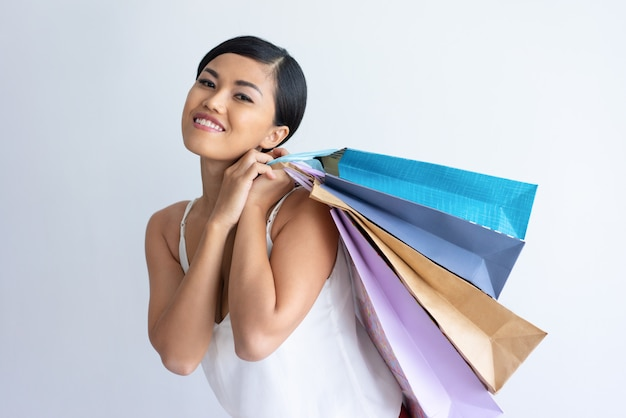 Happy asian lady carrying heap of shopping bags Free Photo