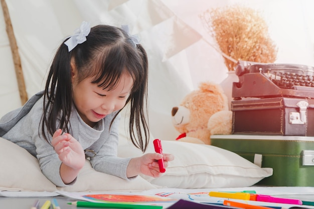 Happy Asian Little Cute Girl Drawing And Painting Color On