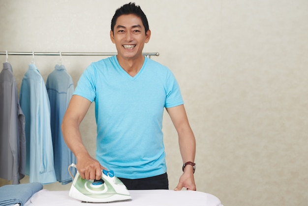 Happy asian man ironing clothes at home Free Photo