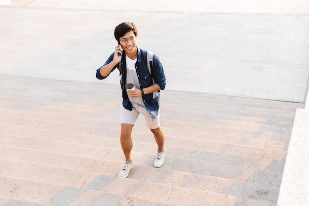 커피 한잔과 함께 야외에서 위층을 걷는 동안 휴대 전화에 얘기하는 행복 한 아시아 사람 프리미엄 사진