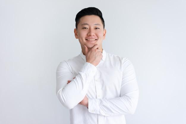 Uomo asiatico felice che tocca mento e che guarda l'obbiettivo Foto Gratuite
