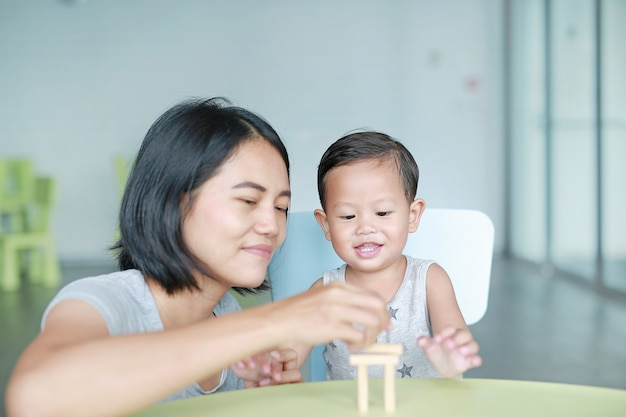 Happy asian mom and little baby boy playing wood blocks tower game for brain and physical development skill in a classroom. focus at children face. child learning and mental skills concept. Premium Photo