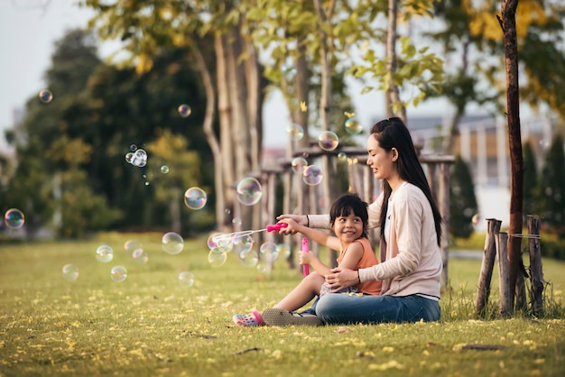 Happy asian mother and daughter blowing bubbles in park outdoors Premium Photo
