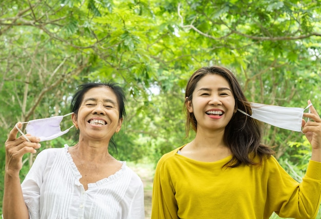 Happy asian mother and daughter traveling outdoors with face mask Premium Photo