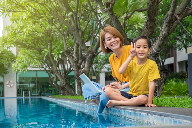 Happy asian mother and son using laptop at outdoors swimming pool Premium Photo