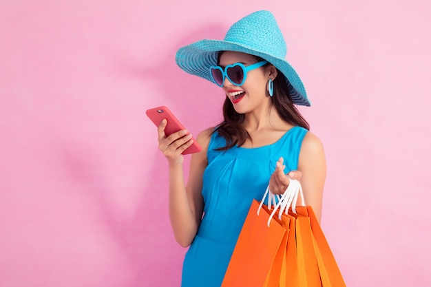 Happy asian pretty girl holding shopping bags and smart phone looking away on pink background Premium Photo