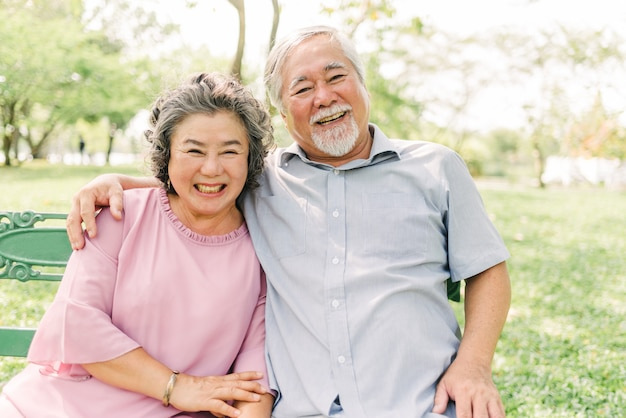 Happy asian senior couple laughing and smiling while sitting in the park Premium Photo