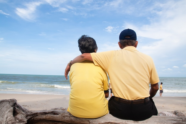 Happy asian senior couple sitting and looking to the beach, back view Premium Photo