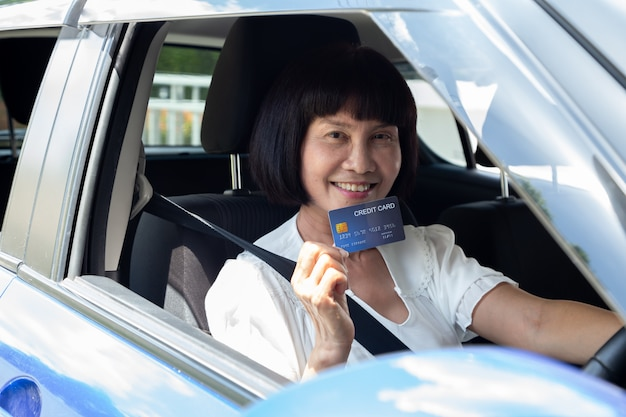 Happy asian senior woman holding payment card or credit card and used to pay for gasoline, diesel, and other fuels at gas stations, driver with fleet cards for refueling car Premium Photo