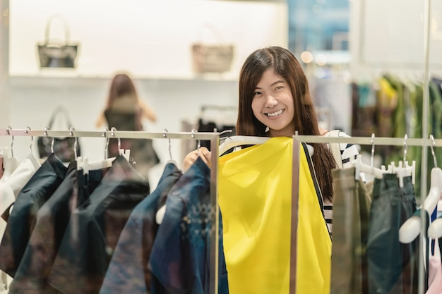 e710c416e Happy asian woman choosing clothes and skirt in glass store shop Premium  Photo