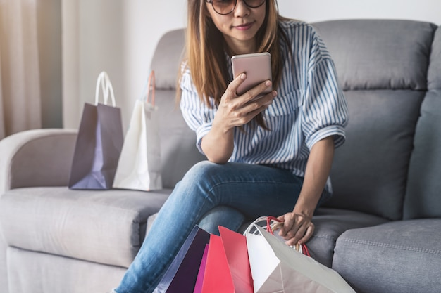 Happy asian woman holding credit card and smart phone Premium Photo