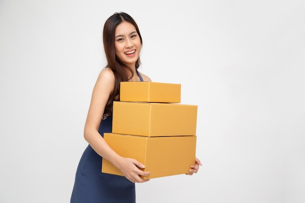 Happy asian woman holding package parcel box isolated on white wall, delivery courier and shipment service concept Premium Photo