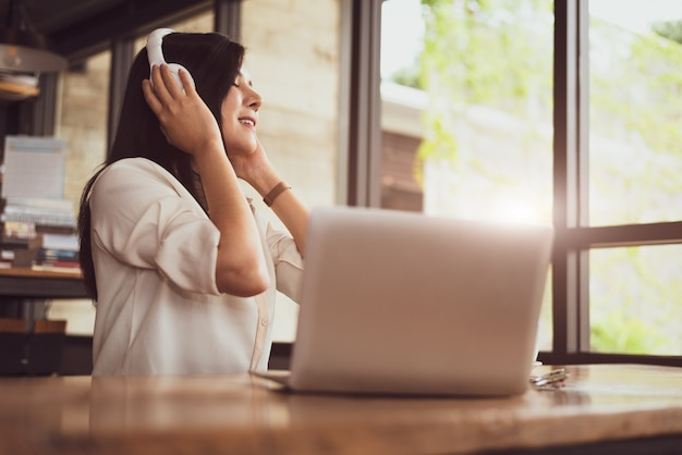 Happy asian woman relaxing and listening music in coffee shop with computer laptop Premium Photo