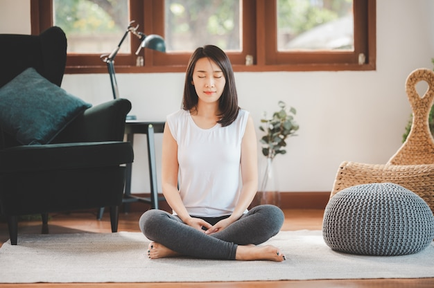 Premium Photo | Happy asian woman sporty attractive practicing meditation  at home