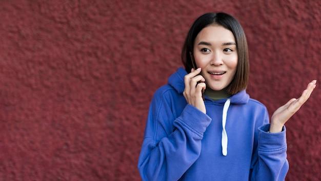 전화 통화하는 행복 한 아시아 여자 무료 사진