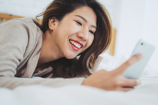 Happy asian women are using smart phone on the bed in morning Free Photo