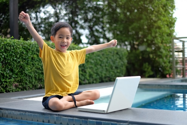 Happy asian young child using computer laptop with hand up at side of swimming pool Premium Photo