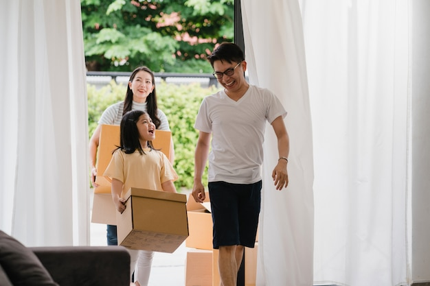 Happy asian young family bought new house. japanese mom, dad, and child smiling happy hold cardboard boxes for move object walking into big modern home. new real estate dwelling, loan and mortgage. Free Photo