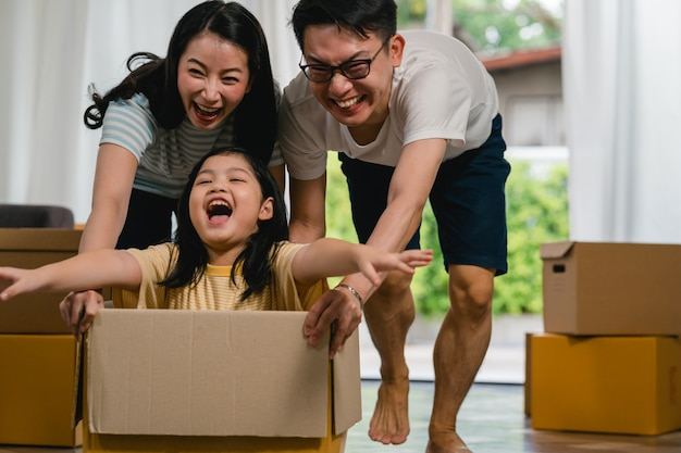 Happy asian young family having fun laughing moving into new home. japanese parents mother and father smiling helping excited little girl riding sitting in cardboard box. new property and relocation. Free Photo