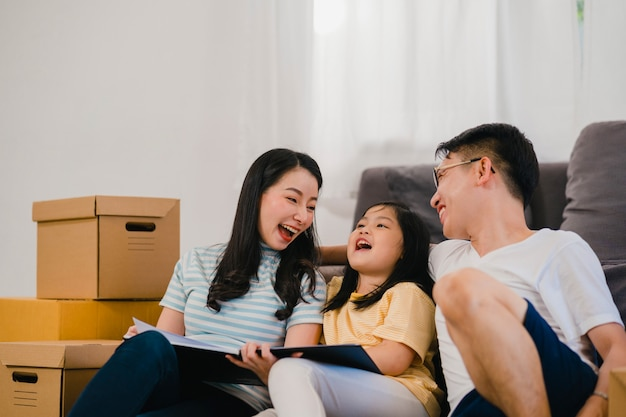 Happy asian young family homeowners bought new house. chinese mom, dad, and daughter embracing looking forward to future in new home after moving in relocation sitting on floor with boxes together. Free Photo