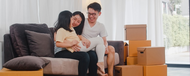 Happy asian young family homeowners bought new house. japanese mom, dad, and daughter embracing looking forward to future in new home after moving in relocation sitting on sofa with boxes together. Free Photo