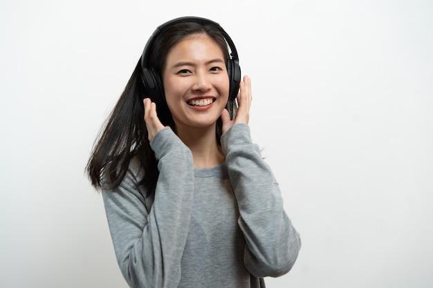 Happy asian young girl listening music from headphones isolated on white background. Premium Photo