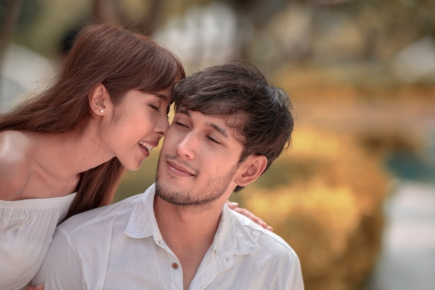 Happy asian young girl peck on the cheek of her boy friend Premium Photo